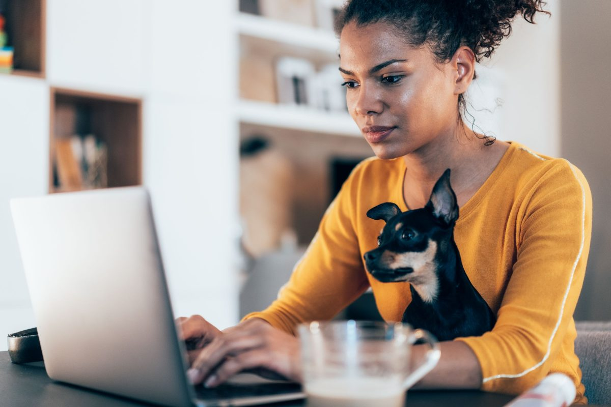A woman and her dog on the computer.